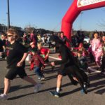 runners of all ages in costumes running under finish line inflatable arch