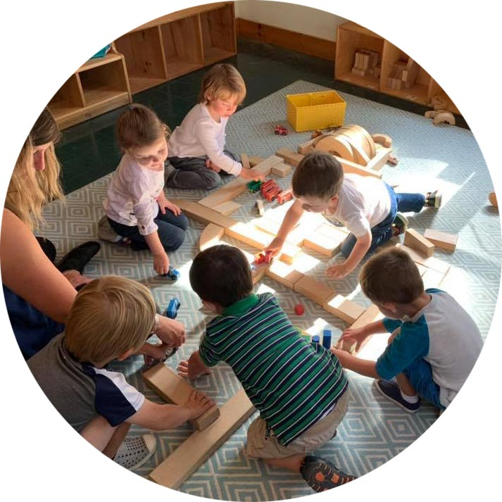 Preschool students collaborating on a toy railway system