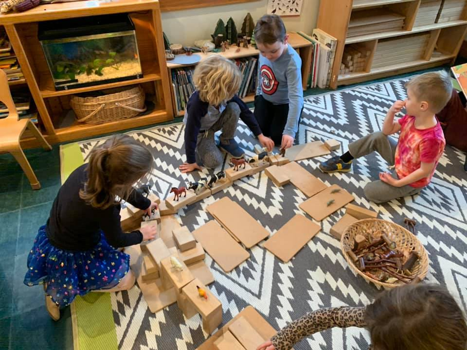 Children building a roadway for zoo animal toys